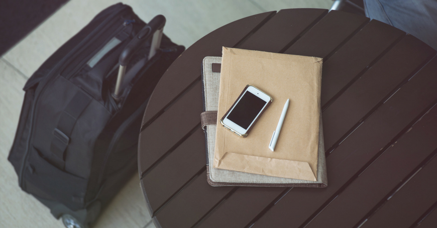 luggage next to table with phone and paperwork