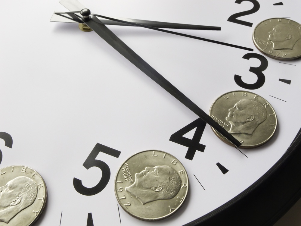 Concept of time is money Eisenhower dollar coins on face of analog clock.jpeg