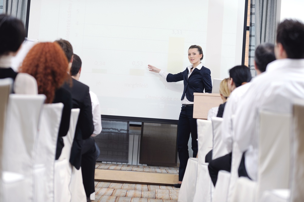 business people at a seminar presentation in bright conference room